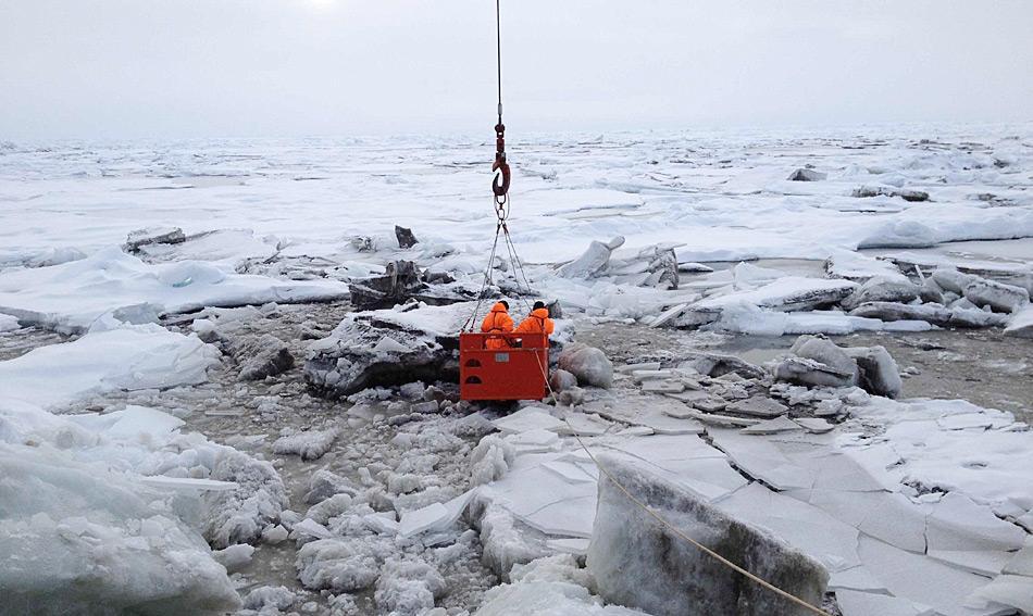 Teilnehmer der Polarstern-Expedition nehmen am 31. August 2014 in der zentralen Arktis Meereisproben. Aus Sicherheitsgründen stehen sie dazu im sogenannten Mummy Chair, der vom Bordkran auf das Eis gehoben wird. Foto: Ruediger Stein, AWI