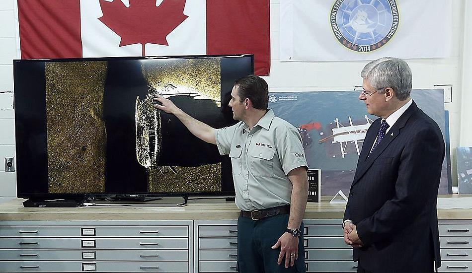 Kanadas Premierminister Stephen Harper beobachtet wie Parkranger Ryan Harris die Entdeckung eines von zwei Schiffen aus der Franklin-Expedition am 9. September in Ottawa erklärt.